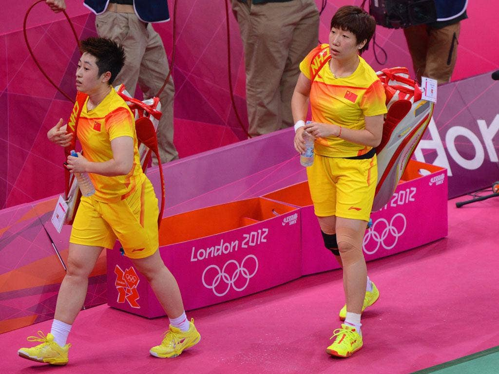Yu Yang (left) and her partner Wang Xiaoli leave the court after their Women's Doubles Badminton match against South Korea