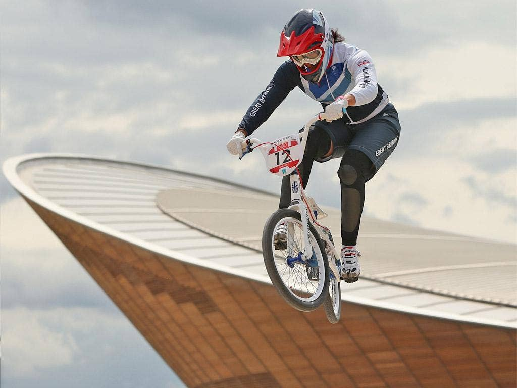 Shanaze Reade trains on the BMX track with the Velodrome in the background yesterday