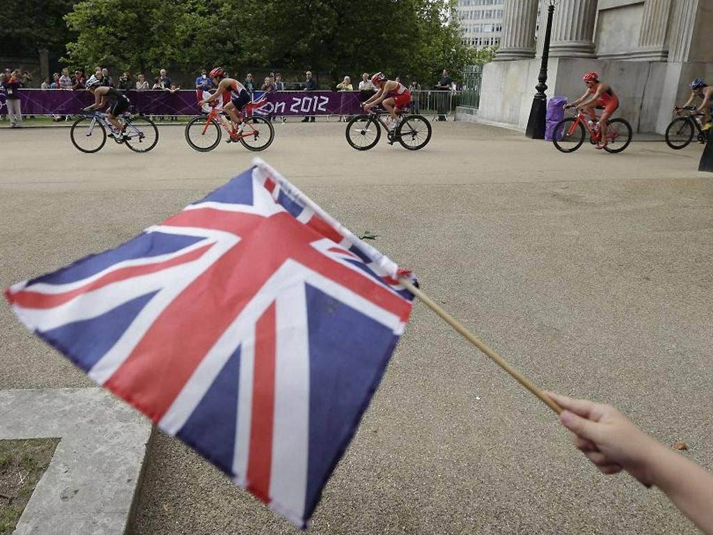 4 August: A boy waves the GB flag as riders pass through Wellington Arch during the women's triathlon