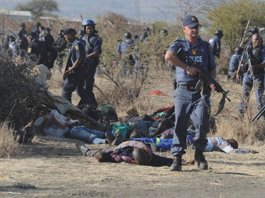 Police surround the bodies of striking miners after opening fire on a crowd  at the Lonmin Platinum Mine near Rustenburg