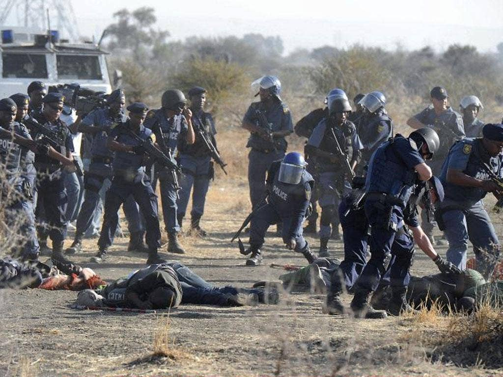 Police check the bodies of miners after opening fire on the strikers outside the Nkageng settlement yesterday