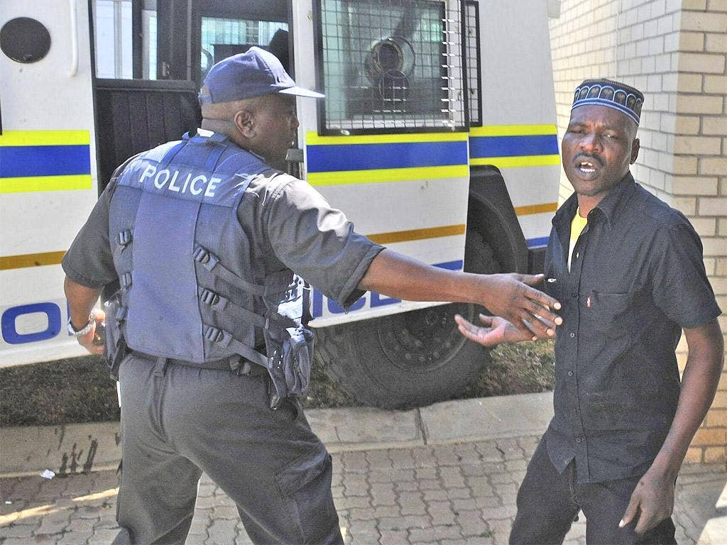 Chris Mahlangu, right, is led away from court after being sentenced