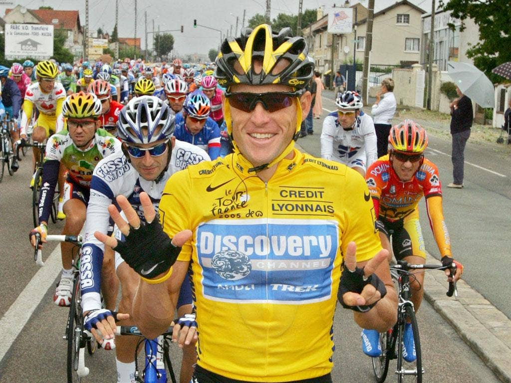 Lance Armstrong signals his seventh win to victory at the Tour de France