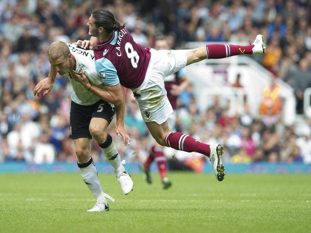 Andy Carroll collides with Fulham's Brede Hangeland