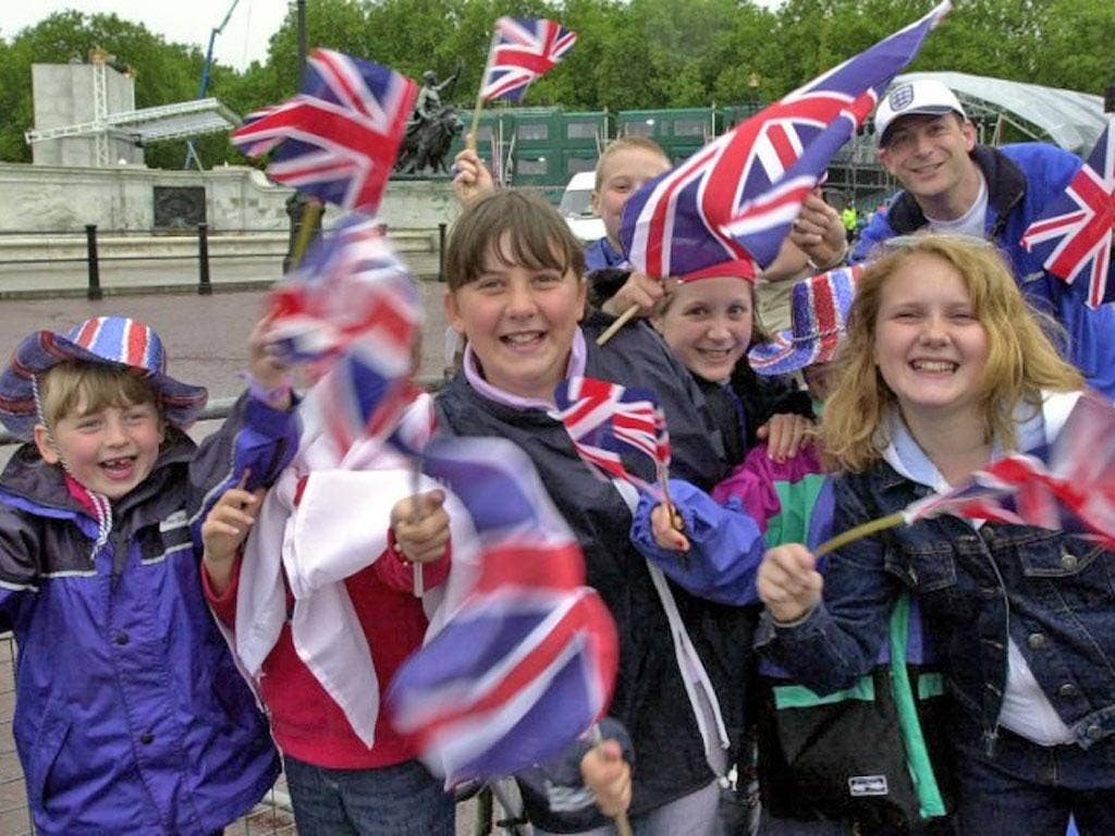 Children wave their Union Jack flags outside Buckingham Palace