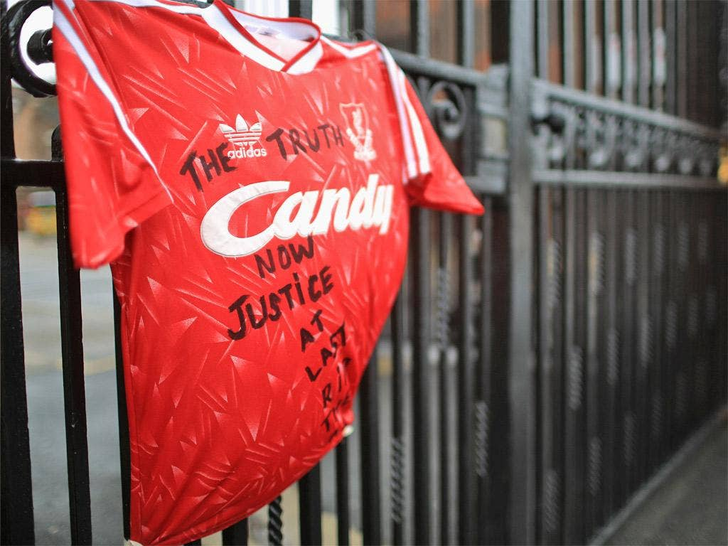 A Liverpool shirt with the message 'The Truth Now Justice At Last, RIP The 96' is tied to the Shankly gates at Anfield stadium