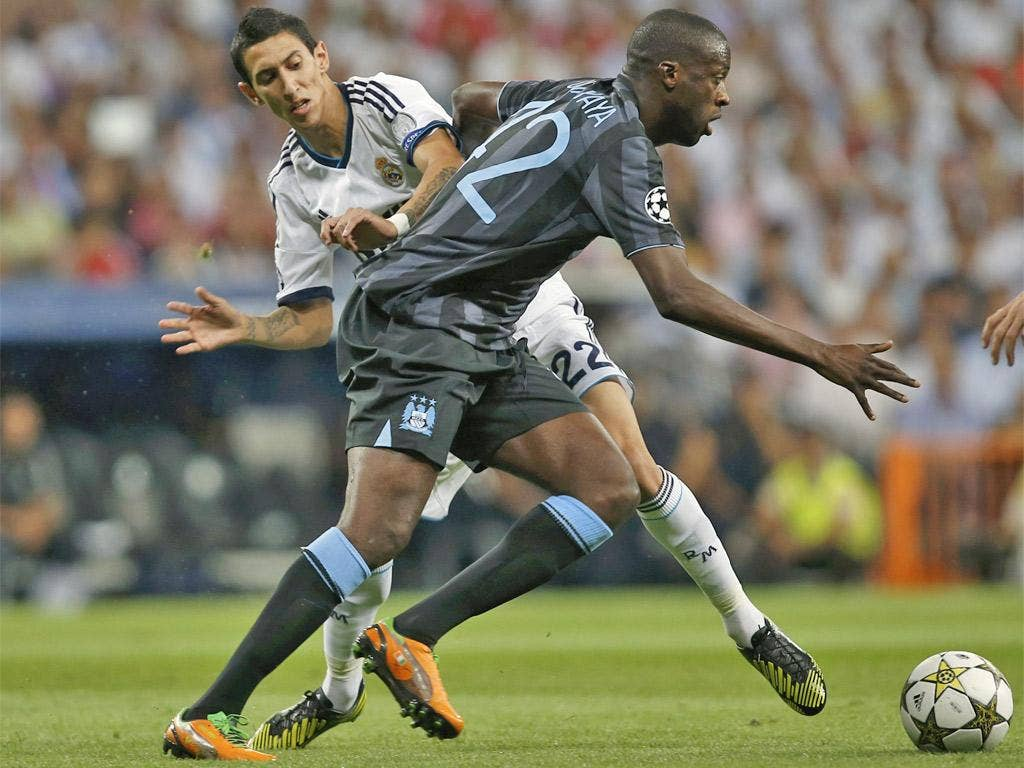 Manchester City's Yaya Toure (right) gives Angel Di Maria the slip in the Bernabeu last night