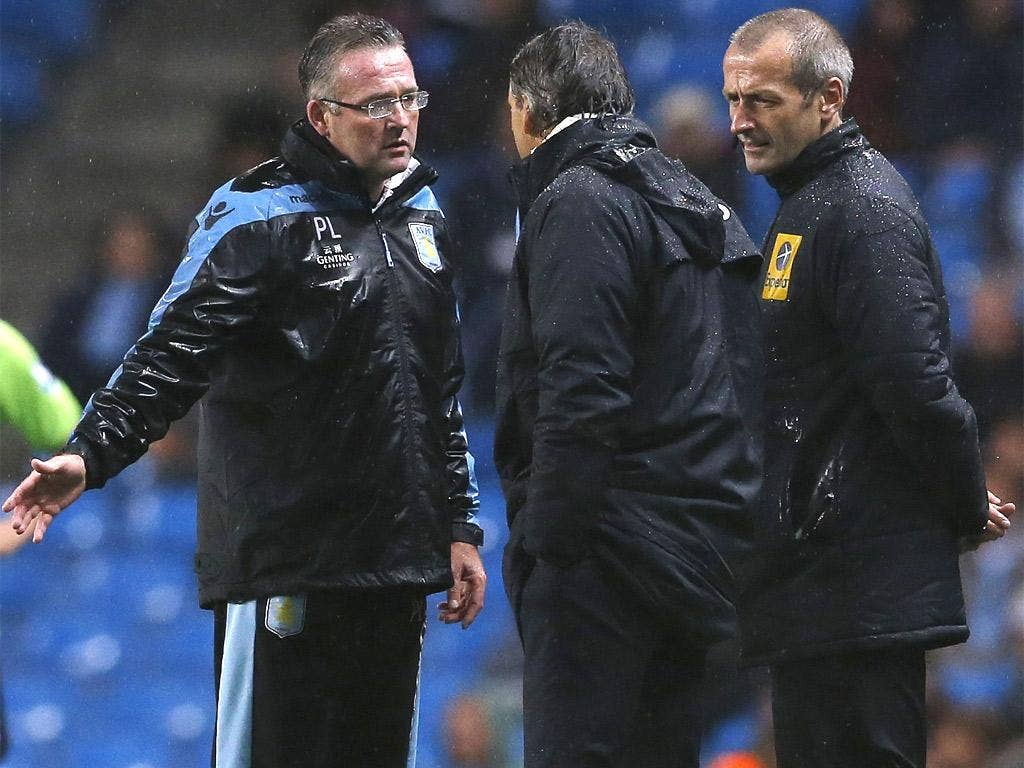 Mancini (centre) has words with the Aston Villa manager, Paul Lambert, after a poor tackle on Gareth Barry