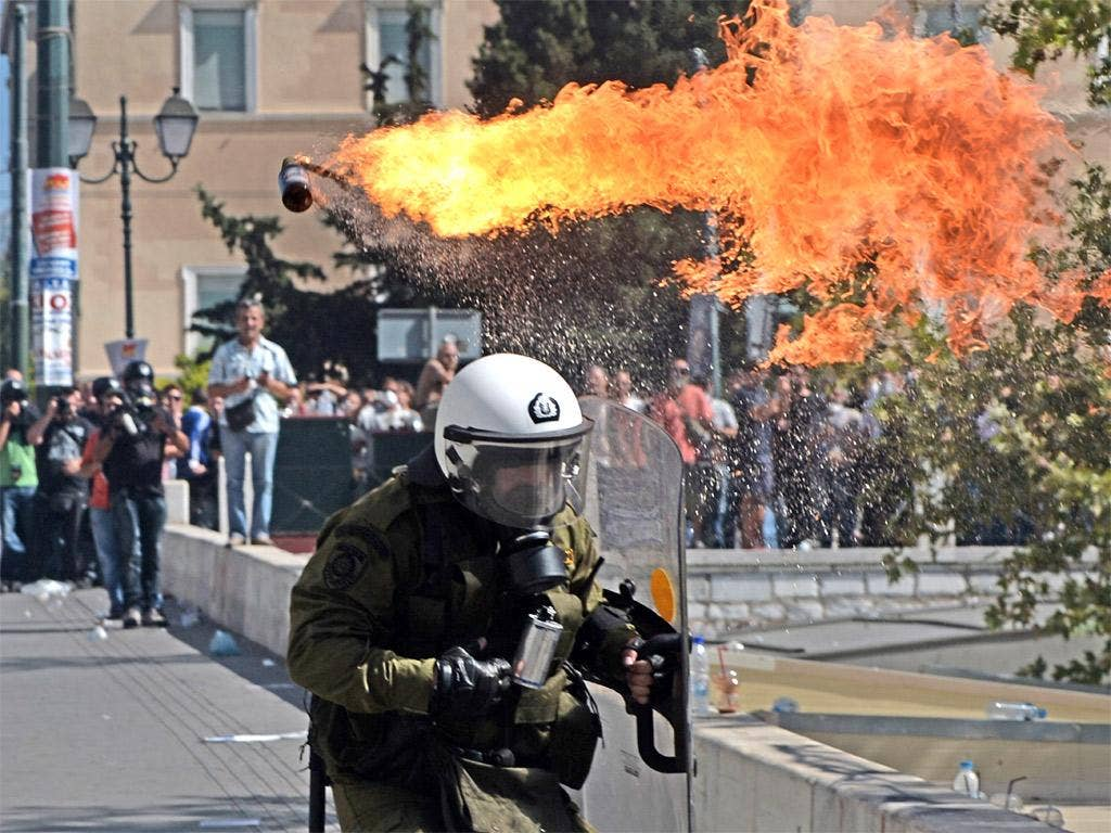 Firebombs explode in front of riot police during clashesi n Greece