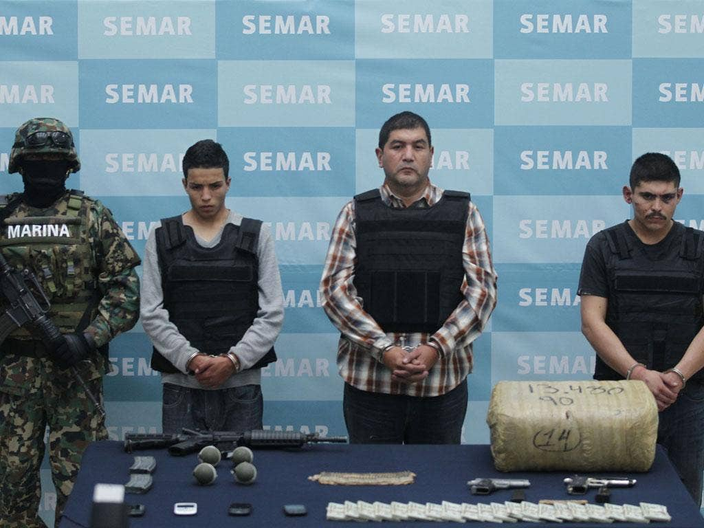 Ivan Velázquez Caballero, in the checked shirt, and two suspects are paraded with drugs and weapons seized during their arrest