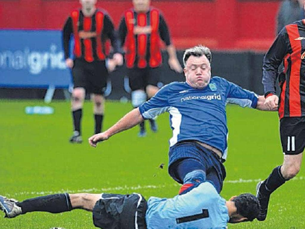 Shadow Chancellor Ed Balls in a tackle at a football match between Labour MPs and journalists in Salford
