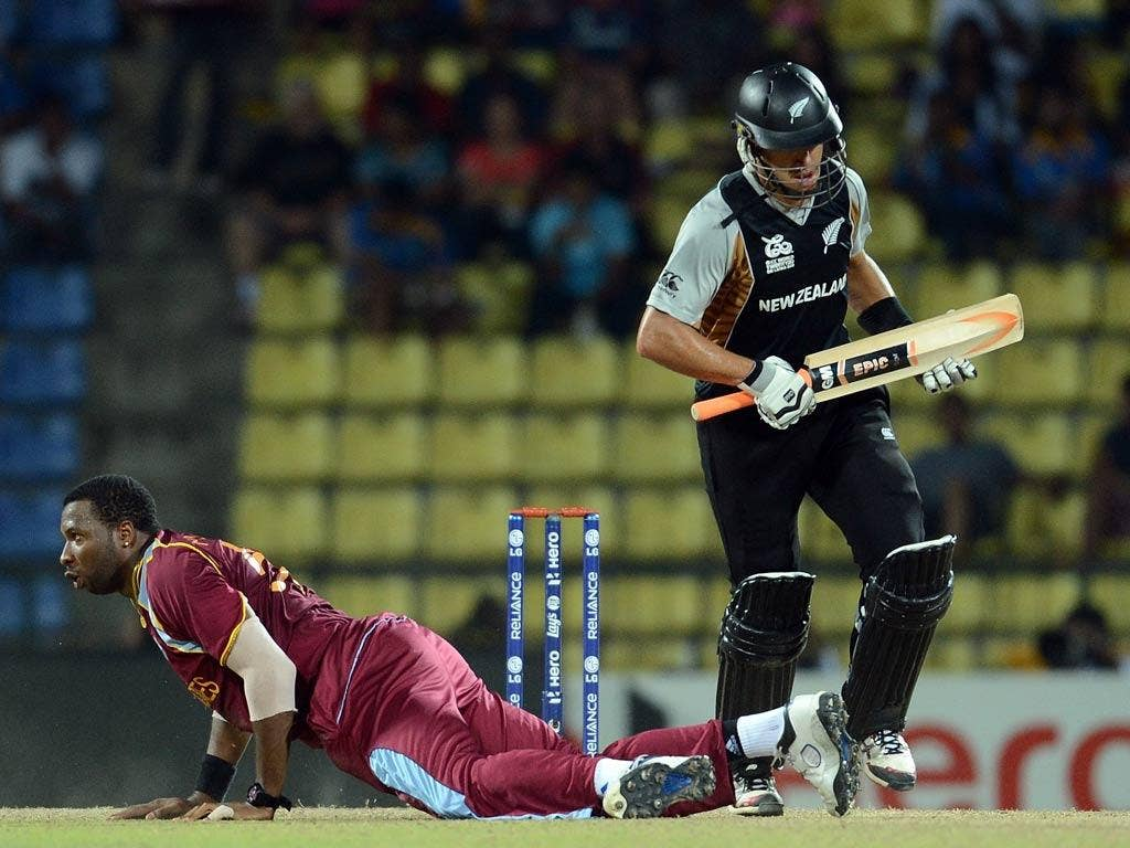 West Indies bowler Kieron Pollard (R) dives to stop a shot as New Zealand cricketer Ross Taylor (L) looks on