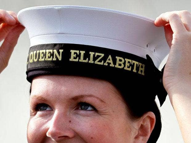 Royal Navy Leading Hand Claire Butler is presented with the first 'cap tally' for being the first crew member to board new aircraft carrier HMS Queen Elizabeth
