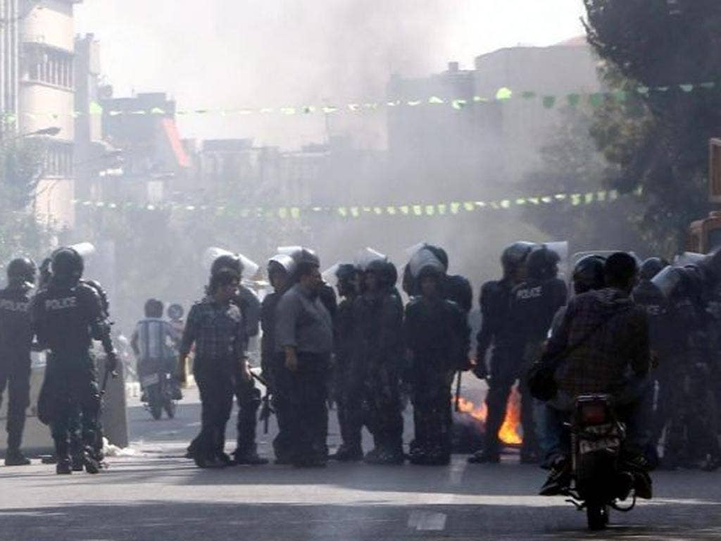 Iranian riot police move in as garbage is set on fire by protestors in central Tehran