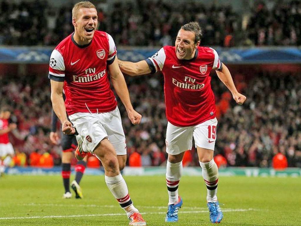 Lukas Podolski celebrates scoring the second Arsenal goal with Santi Cazorla during the UEFA Champions League