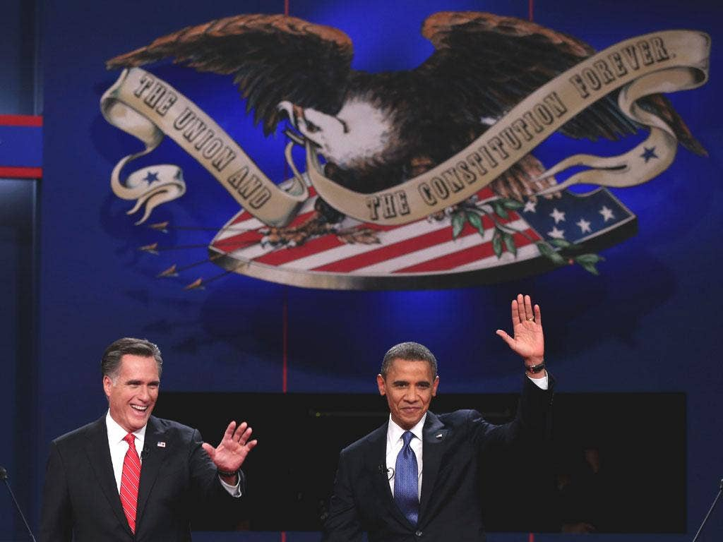 Barack Obama and Mitt Romney wave to the audience during the Presidential Debate in Denver