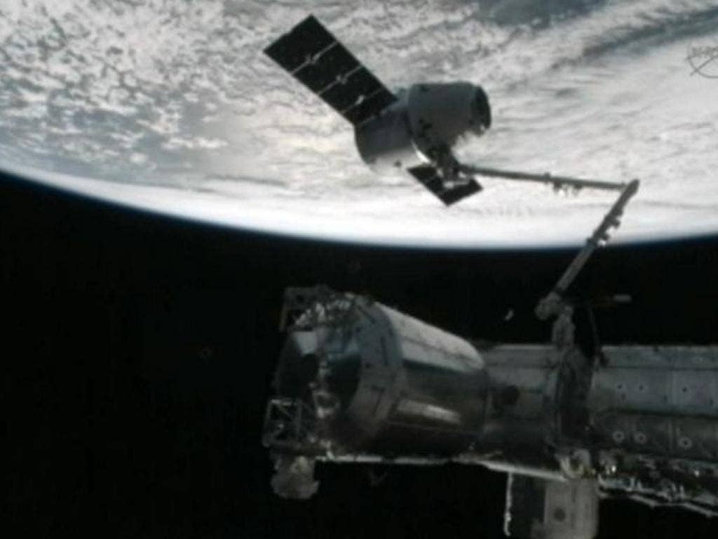 The capture of the Dragon capsule by a robot arm on the International Space Station