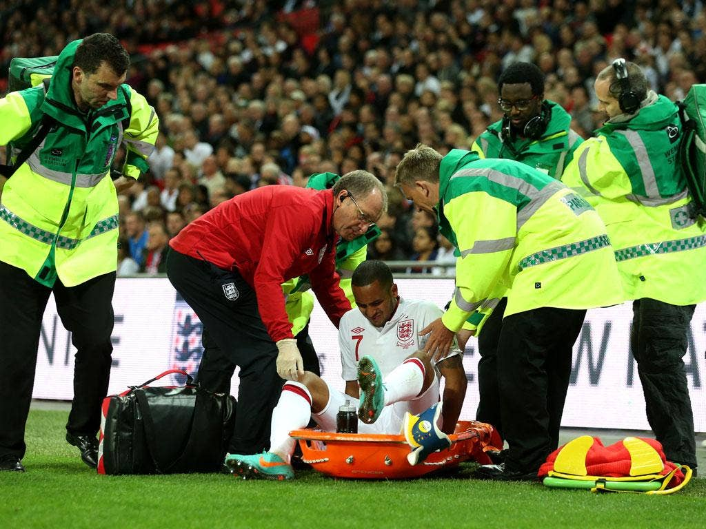 Theo Walcott receives assistance after picking up an injury against San Marino last night