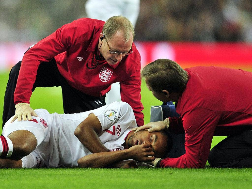 Theo Walcott is attended by medical staff as he lies injured after clashing with San Marino's goalkeeper Aldo Simoncini