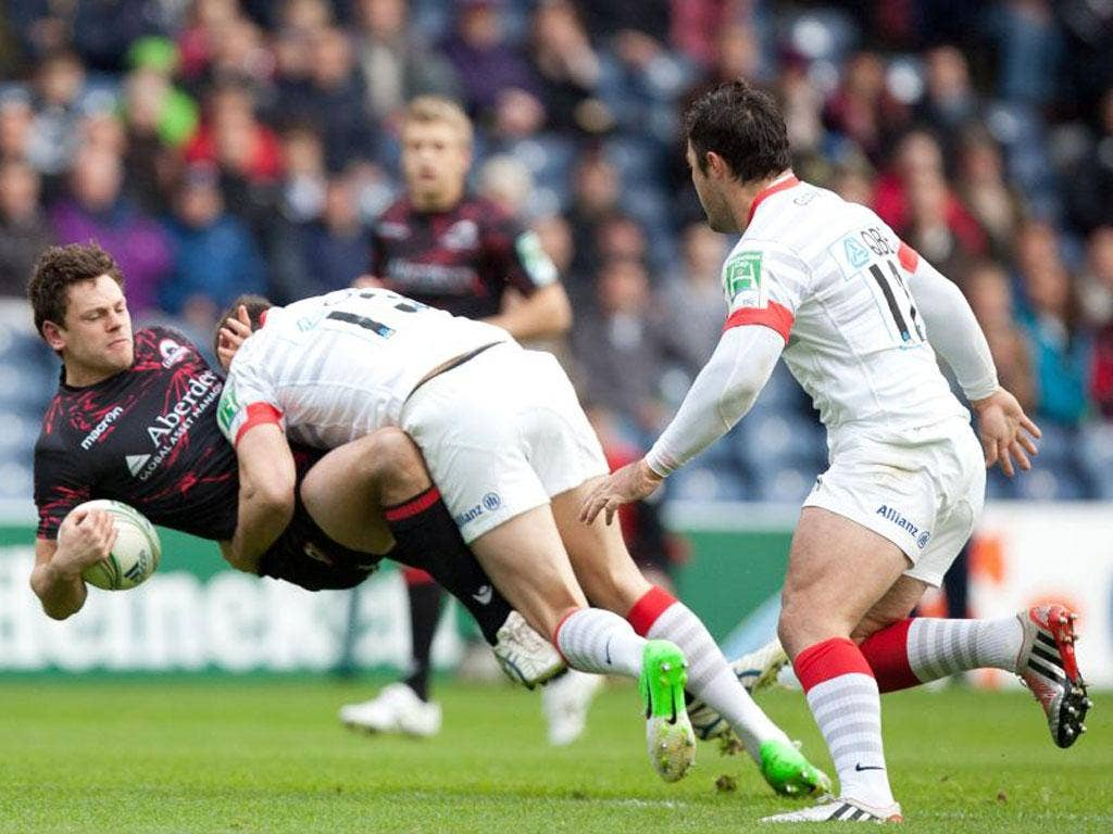 Edinburgh's Nick De Luca is tackled by Saracens' Joel Tomkins