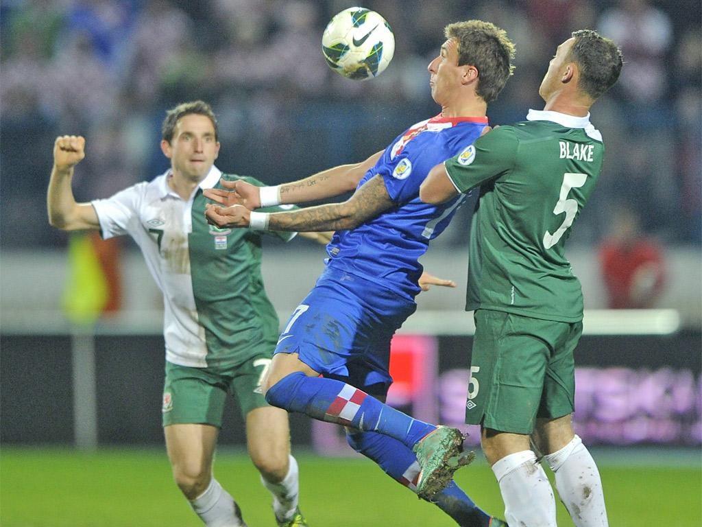 Croatia's Marijo Mandzukic keeps the ball from Joe Allen and Darcy Blake of Wales