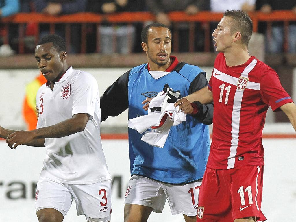 Andros Townsend separates his team-mate Danny Rose and Sasa Markovic of Serbia