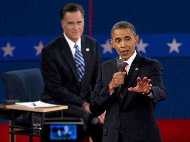 President Barack Obama speaks as Republican presidential candidate Mitt Romney listens during the second presidential debate