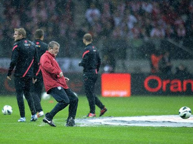 England manager Roy Hodgson tests the condition of the pitch in the pouring rain before the World Cup Group H Qualifying match at the National Stadium in Warsaw