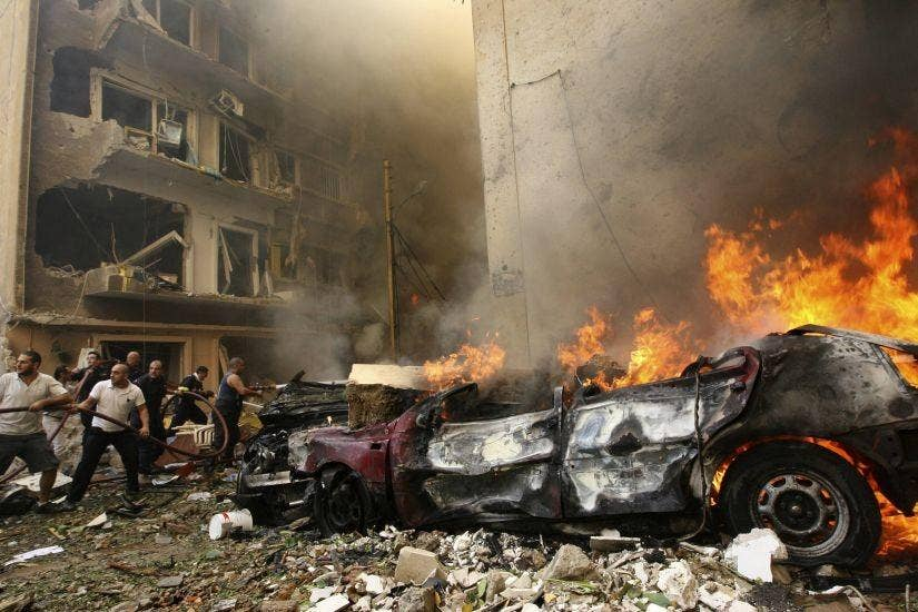 Firefighters try to extinguish a fire as a car burns at the scene of an explosion in Ashafriyeh, central Beirut