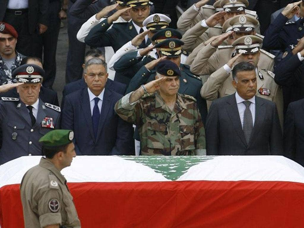 Top Lebanese military brass salute during the funerals of top intelligence chief General Wissam al-Hassan and his bodyguard outside the headquarters of the Internal Security Forces ahead of their funeral procession in downtown Beirut