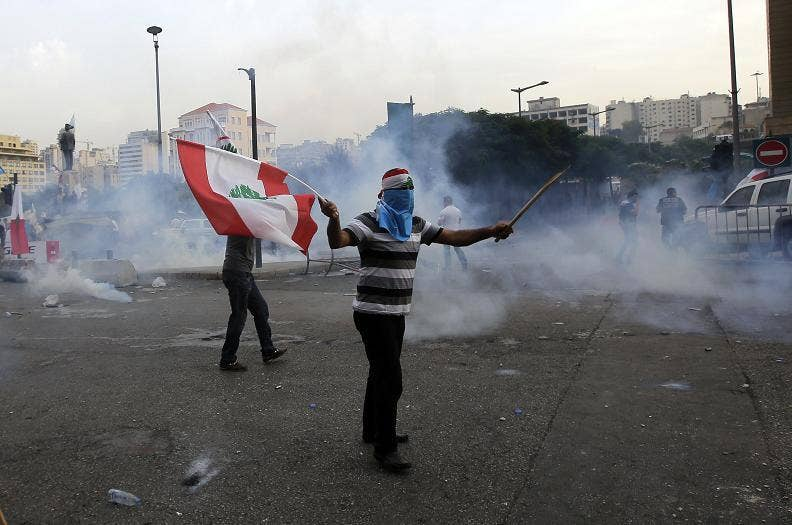 A Lebanese supporter of the March 14 movement, which opposes the Syrian regime of President Bashar al-Assad, demonstrates waving his national flag, as other protesters tried to storm the governmental palace, after the funeral of top intelligence chief Gen