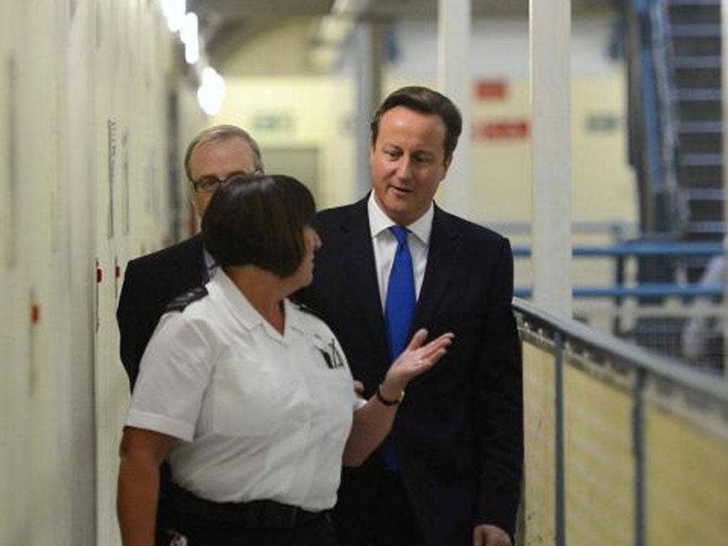 David Cameron is escorted around C wing during his visit to Wormwood Scrubs Prison in west London yesterday
