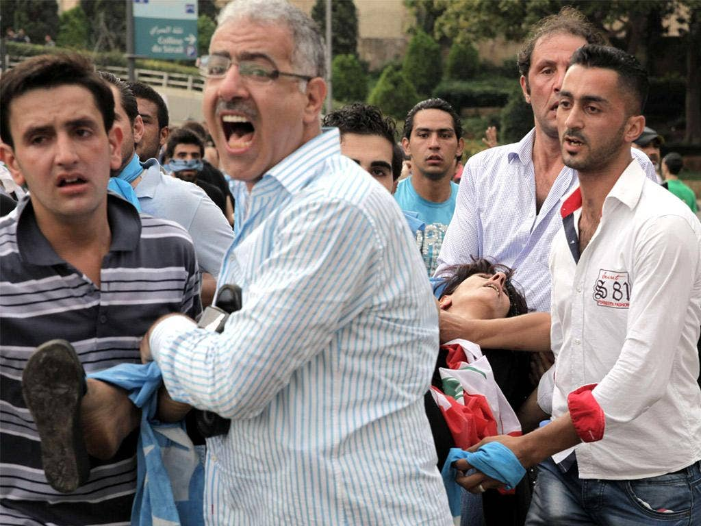 Supporters of the March 14 bloc carry a wounded woman during protests on Sunday