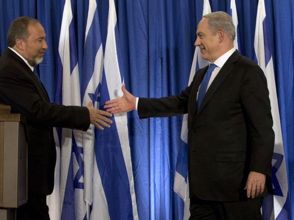 Israel's Foreign Minister, Avigdor Lieberman, left, and Prime Minister Benjamin Netanyahu seal the deal in Jerusalem