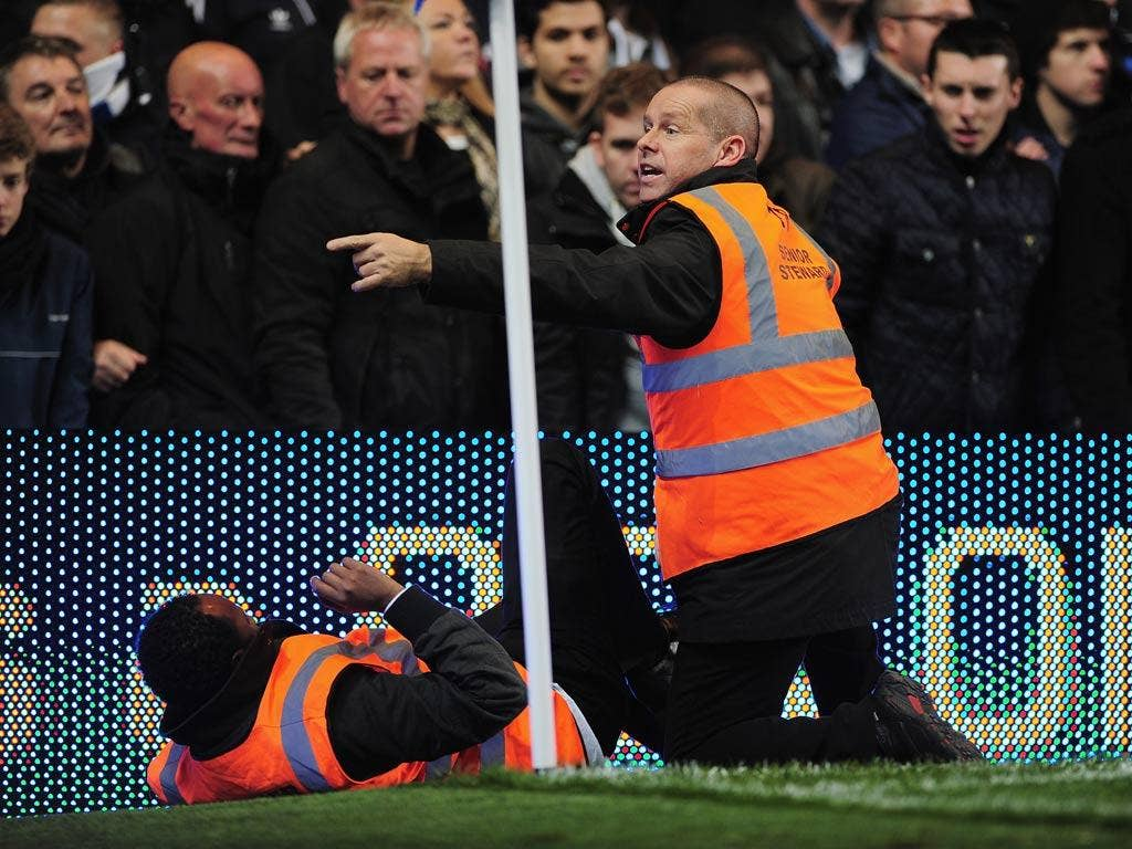 A steward is helped by a fellow steward during the Barclays Premier League match between Chelsea and Manchester United at Stamford Bridge