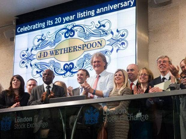 JD Wetherspoon founder Tim Martin (centre) marks his company's 20 years as a listed company today by opening trading on the London Stock Exchange