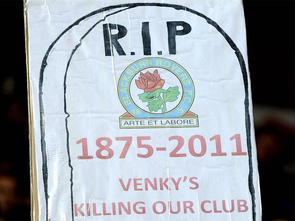 A Blackburn Rovers fan holds up a poster in protest against the club's owners Venkys
