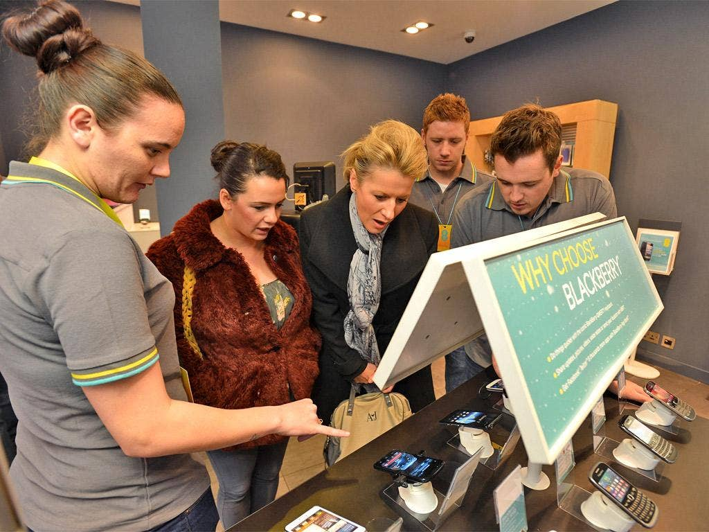Shoppers at an EE store in Glasgow learn about 4G mobile phones