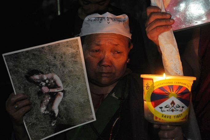 An exile Tibetan woman cries while holding a photograph of a Tibetan youth from eastern Tibet who on September 29 allegedly burned himself in protest against Chinese rule, during a candlelight vigil in McLeod Ganj, Dharamsala, on September 30, 2012. Twent