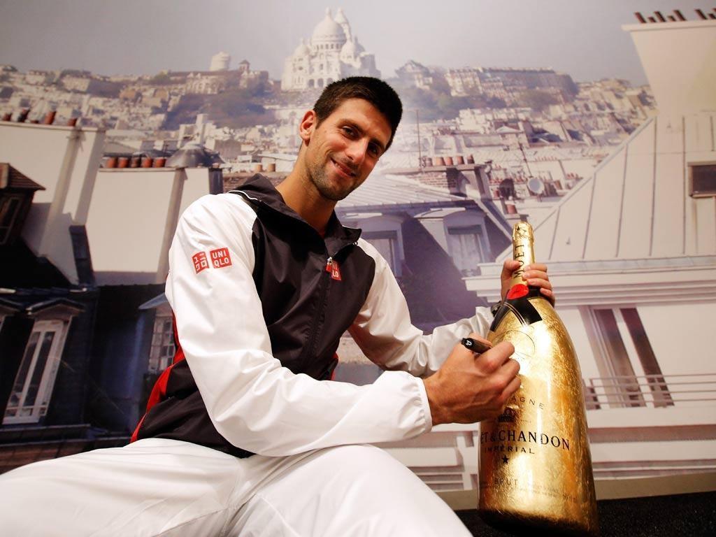 Novak Djokovic signs the bottle