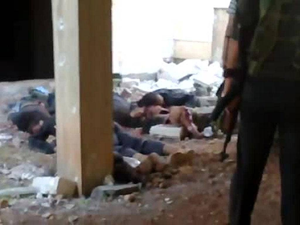 An image grab taken from a video uploaded on YouTube on November 1, 2012 shows rebel fighters standing near alleged bodies of Syrian soldiers
