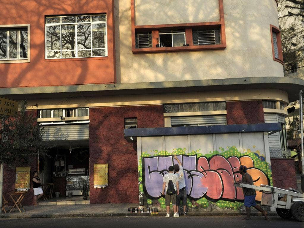 Spray day: Two street artists painting a news stand in Sao Paulo's Paraiso neighbourhood