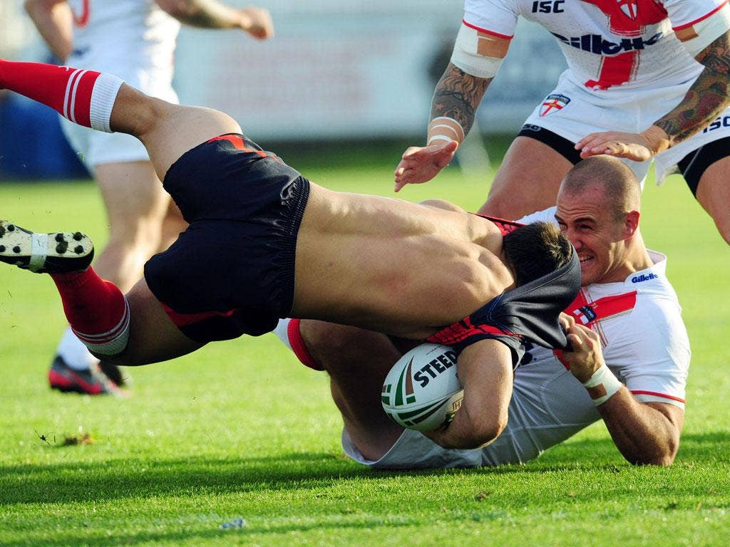 Getting shirty: France centre Damien Cardace almost loses his jersey as he is tackled by England forward Lee Mossop