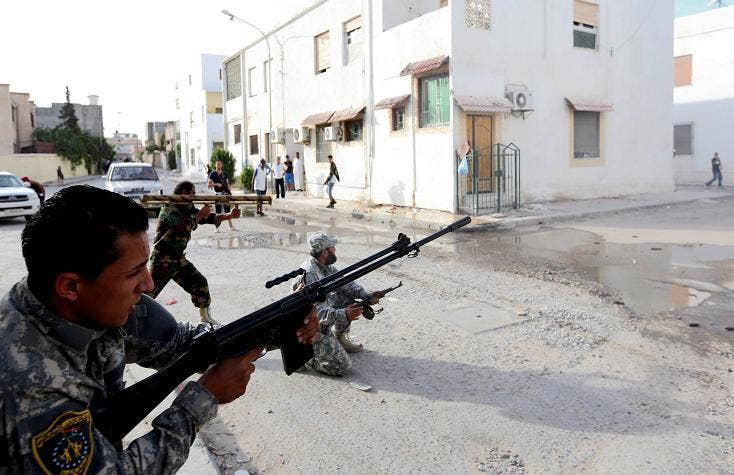 Libyan state security forces known as the National Mobile Forces fire to disband clashes between armed groups near Zawiya street in the Libyan capital, Tripoli