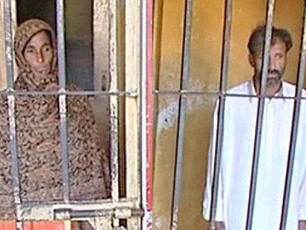 Muhammad Zafar, right, and his wife Zaheen behind bars