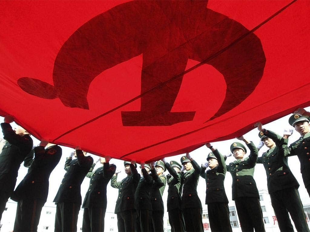 Soldiers in Beijing hold up the Communist Party flag