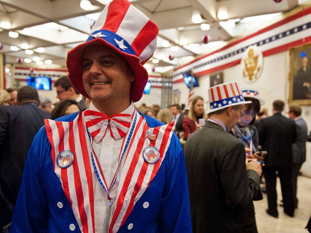 A reveller awaits results at the US Embassy in London during the traditional election night party