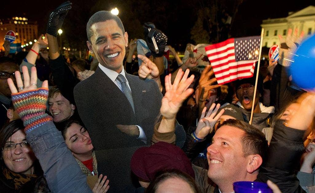 People celebrate in front of the White House with a cardboard cut-out of the President