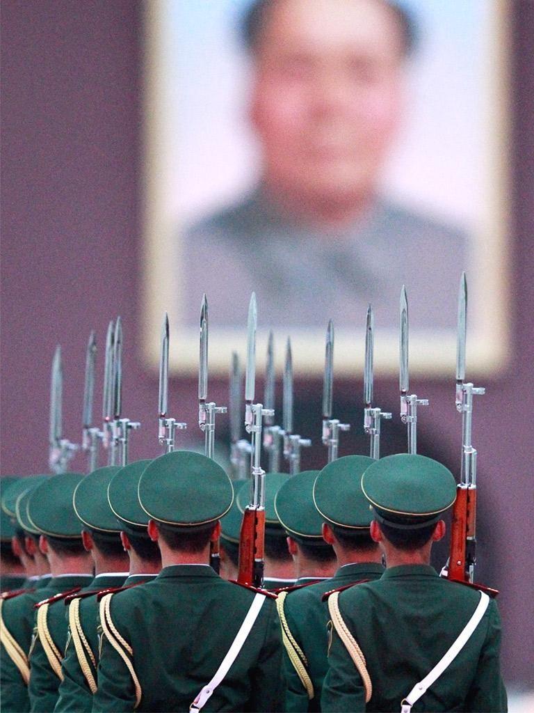 Soldiers march in Beijing below a portrait of Mao Zedong