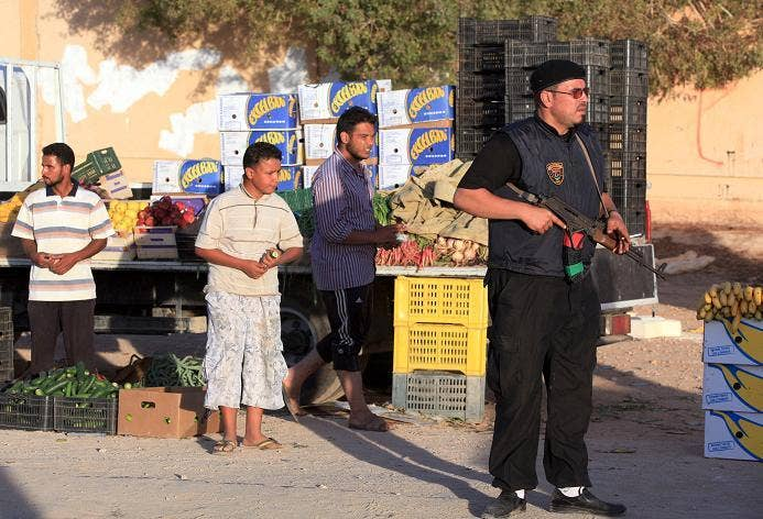 A pro-government Libyan fighter holds his gun as people shop at a market in the city of Bani Walid